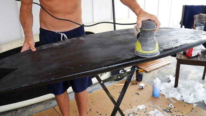 Sanding a surfboard